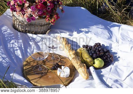 Wooden Stand With Two Glasses Of Champagne, Grapes, Baguette And Camembert Cheese On White Blanket I