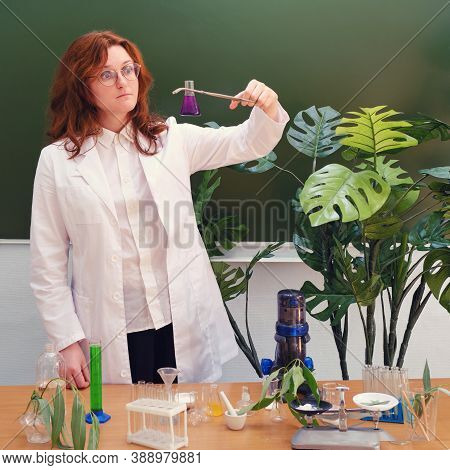 Woman Ecologist With Chemical Flask And Funnel For Liquid In Hand. Analyzes, Tests And Research In T