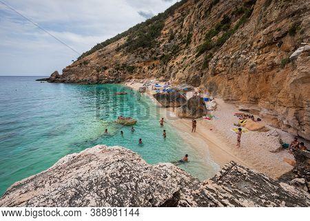 Cala Mariolu, Sardinia. August 03, 2020: Beach In A Natural Cove In Sardinia In Italy. Numerous Peop