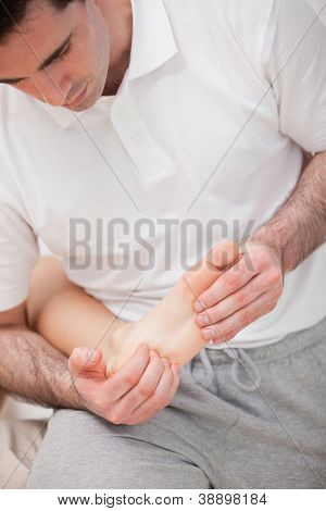 Reflexologist massaging the sole of the patient in a room