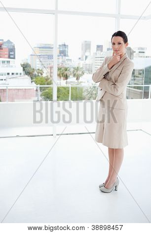 Serious businesswoman standing in front of the bright window in a thoughtful way