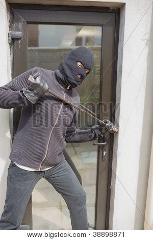 Burglar breaking into home using crow bar through back door
