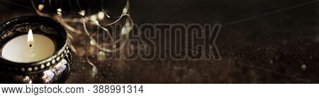 Burning Christmas Candle On Dark Shiny Background. Symbol For A Religious Ritual And Spiritual Medit