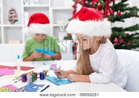 Kids making christmas or seasonal greeting cards
