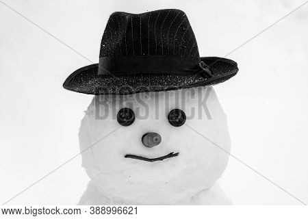 Funny Snowman In Stylish Hat And Scarf On Snowy Field. New Year Concept. Cute Little Snowman Outdoor