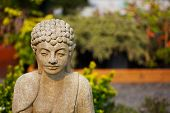 Shallow focus image of concrete Buddha  in an asian garden poster