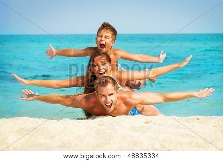 Happy Young Family with Little Kid Having Fun at the Beach. Joyful Family. Travel and Vacation poster