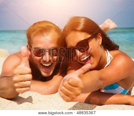 Happy Couple in Sunglasses having fun on the Beach. Summer Vacation. Laughing Family enjoying Nature over Sea Background. Attractive Man and Woman at the Beach  poster