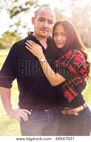 Happy young couple portrait, asian woman, caucasian man, hugging tenderly in outdoor environment and beautiful light