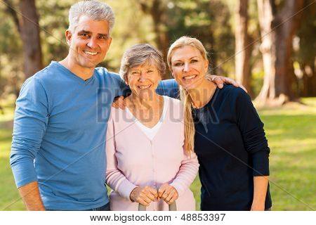 loving mid age couple and senior mother outdoors in forest