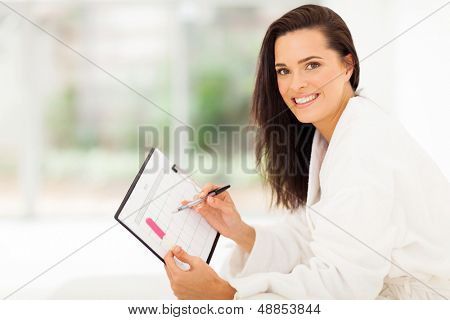 elegant young woman planning her pregnancy in bedroom at home