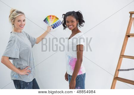 Housemates picking color for blank wall and smiling at camera in their new home