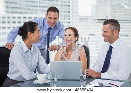 Cheerful colleagues around laptop working together in bright office
