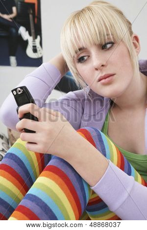 Beautiful teenage girl reading text message on mobile phone at home