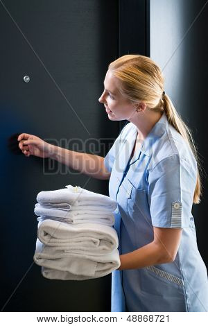 Hotel room service - young chambermaid standing in front of a room door in a suite with fresh towels