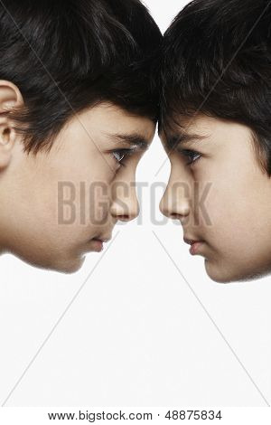Side view closeup of preadolescent brothers with head to head isolated over white background