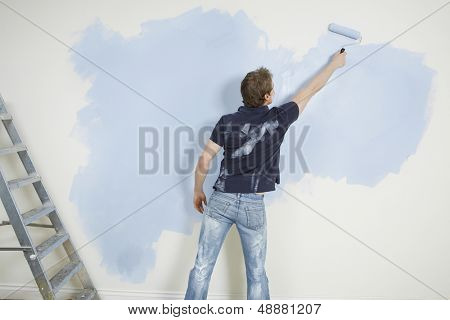 Rear view of young man painting wall with paintroller in unrenovated house