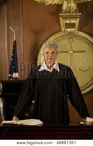 Portrait of confident senior female judge standing in court room