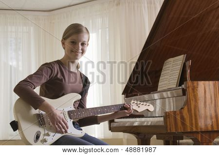 Portrait of a young girl playing the guitar