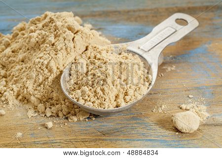 maca root powder - a measuring tablespoon and pile on wooden surface