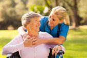 caring nurse with senior patient outdoors poster