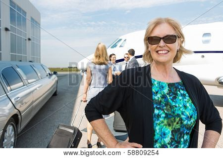 Portrait of happy mature businesswoman with limousine and private jet in background
