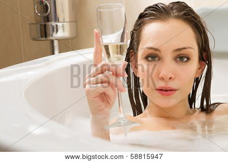 A young beautiful  woman is enjoying a bath with a glasses of champagne