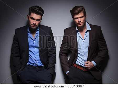 serious male models posing against gray wall in studio