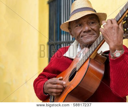 HAVANA,CUBA - JANUARY 15, 2014:Old afrocuban street musician playing the guitar next to a colonial house.2 850 000 foreign tourists visited Cuba in 2013,many of them attracted by its distinct culture