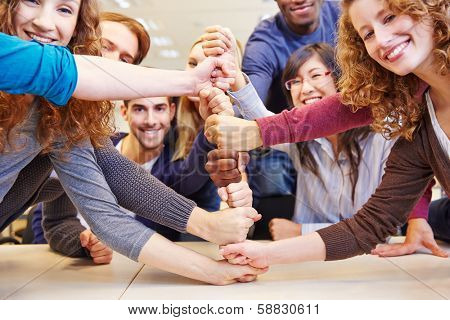Students stacking fists for cooperation and teamwork in a university