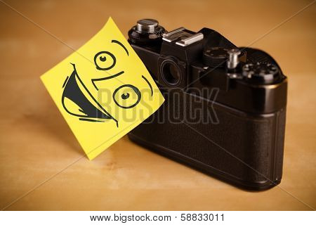 Drawn smiley face on a post-it note sticked on a photo camera