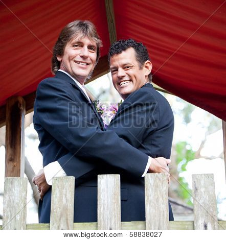 Portrait of a newly married gay couple embracing on a playground in the park.