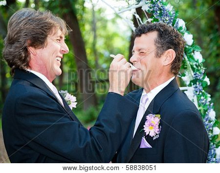 One groom at a gay wedding feeding cake to his husband and laughing.
