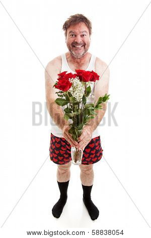 Humorous photo of a scruffy looking middle aged man in his underwear holding a bouquet of roses for his sweetie.  Full body isolated on white.
