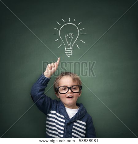Schoolboy standing in front of a blackboard with a bright idea light bulb above his head concept for innovation, imagination and inspirational ideas poster