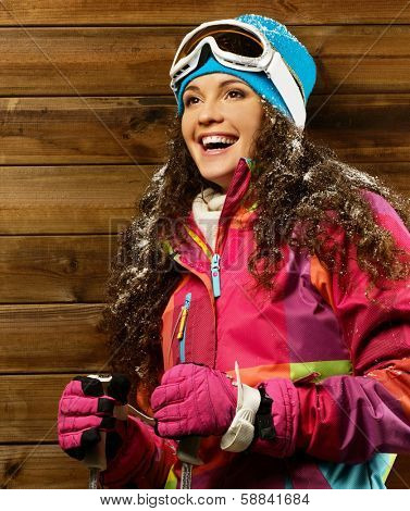 Smiling woman with ski poles standing against wooden house wall