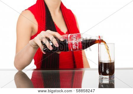 NAKHODKA, RUSSIA - JANUARY 18, 2014: Asian girl pours a Coca-Cola from a bottle into a glass. Coca-Cola is a carbonated soft drink sold in stores, restaurants, and vending machines worldwide.