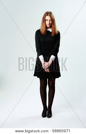 Full-length portrait of a young thoughtful woman in black dress on gray background