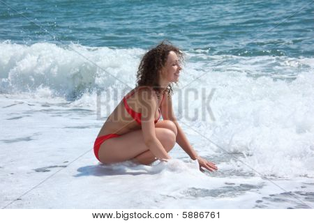 Beauty Girl Sits In Sea Surf