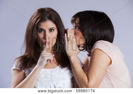 Two female friends sharing a secret