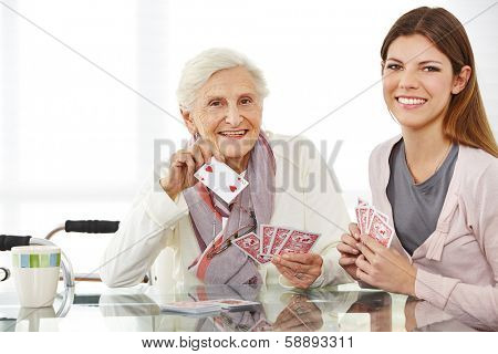 Young eldercare nurse playing cards with happy senior woman