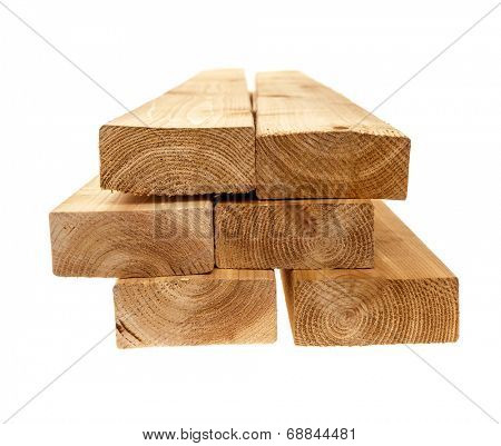 Edge of six cedar two by four lumber boards stacked on white background