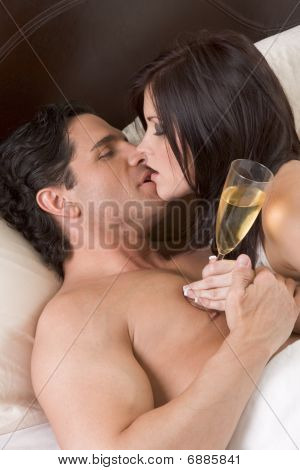 Loving Young Sensual Couple With Champagne In Bed