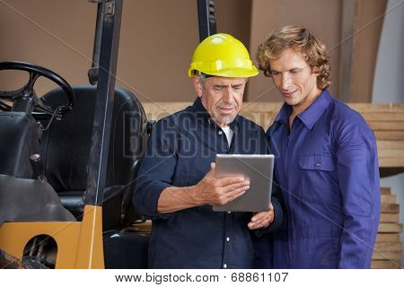 Manual workers using digital tablet together in workshop