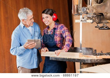 Portrait of young female carpenter with senior colleague using digital tablet in workshop