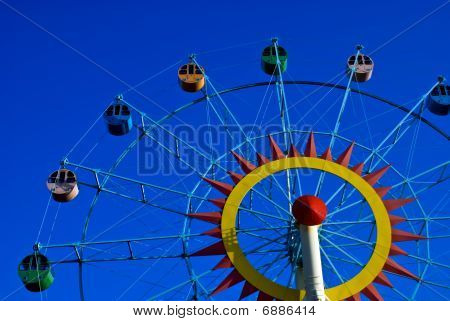 A Colorful Ferris Wheel Shot Against A Blue Sky, Left View