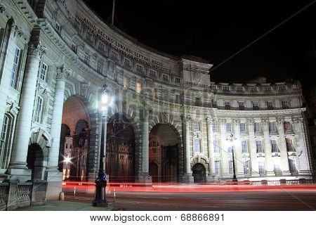Admiralty Arch at night with headlight and tailight light trails, which was completed in 1912 and commissioned by Edward V11 in memory of his mother Queen Victoria. It provides an archway and pedestrian access between The Mall and Trafalgar Square poster