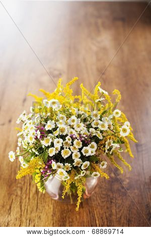 Wildflowers bouquet in glass vase on wooden background poster