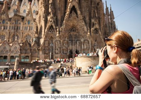 Young woman taking picture of Sagrada Familia