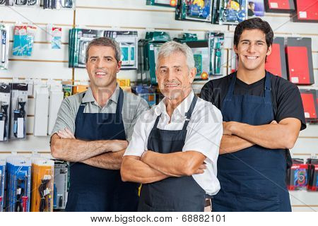 Portrait of happy salesmen standing arms crossed in hardware store